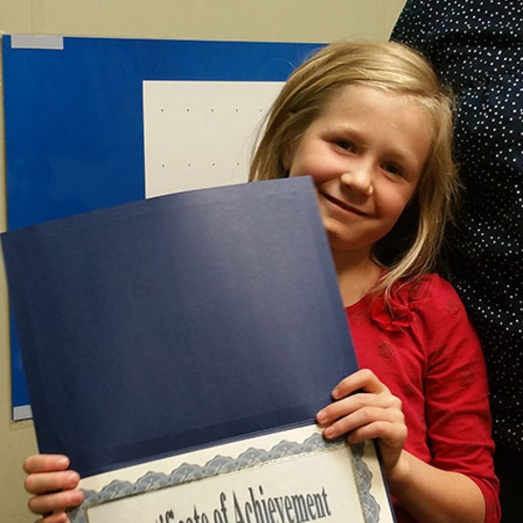 young student holding blue graduation certificate